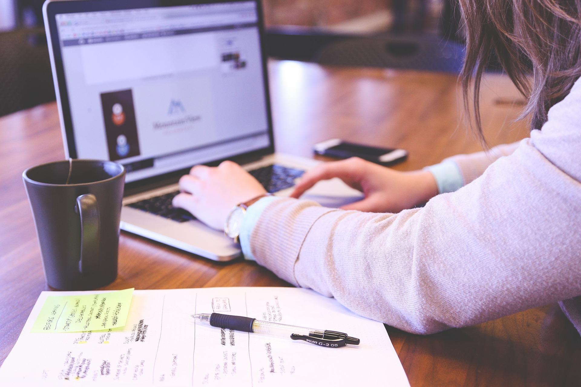 diseñando banner display, mujer computador mac, mesa, café, papeles, trabajando